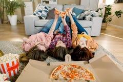 Pizzalieferung, Frauenpartei Glückliche drei Mädchen, die das Mittagessen, Pizza, Popcorn und Wein zu Hause Ernte, Nahaufnahme es lizenzfreies stockfoto