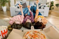 Pizzalieferung, Frauenpartei Gl?ckliche drei M?dchen, die das Mittagessen, Pizza, Popcorn und Wein zu Hause Ernte, Nahaufnahme es lizenzfreies stockbild