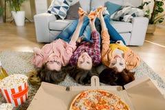 Pizzalieferung, Frauenpartei Gl?ckliche drei M?dchen, die das Mittagessen, Pizza, Popcorn und Wein zu Hause Ernte, Nahaufnahme es lizenzfreies stockfoto