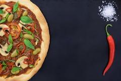 Pizzamargheritaen tjänade som med det chilipeppar och havet som var salta på täckningmagasinet kopiera avstånd Arkivfoton