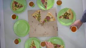 Pizzapartij, bedrijf van vriendenhanden die plakkenpizza en lege plaat en gerinkel plastic glazen met bier op lijst nemen stock videobeelden