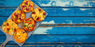 Pizzas arranged on wooden table Royalty Free Stock Photography