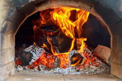 Pizzas baking in an open firewood oven Stock Images