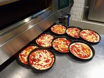 Pizzas being readied for baking Royalty Free Stock Images