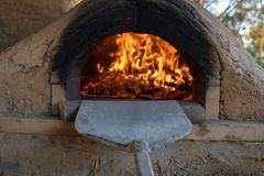 Pizzas cooking in stone and cob pizza oven Stock Photo