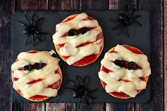 Pizzas de la momia de Halloween mini en el servidor de la pizarra con las arañas Foto de archivo