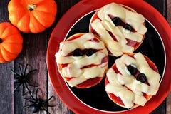 Pizzas de la momia de Halloween mini en la placa negra y anaranjada Fotos de archivo