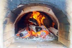 Pizzas faisant cuire au four dans un four ouvert de bois de chauffage Image stock