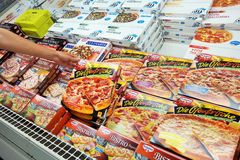Pizzas in Freezer. GERMANY - AUGUST 2015: Freezer contains cartons frozen pizza for home cooking in a REAL hypermarket in Germany Stock Image