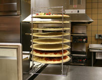 Pizzas in Rack  (Focus on pizzas) Royalty Free Stock Images