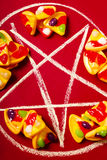 Pizzas and Satanic symbols. Evil still-life photo on a chalked out pentagram with small pizzas slices. Symbols of occultism Stock Photos