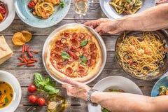 Pizzasalami in den Kochhänden Dienendes diavolo Pizza des Chefs in der mittleren Tabelle voll von italienischen Mahlzeiten stockbild