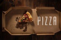 Pizzascheibe in im Lieferungskasten auf dem Holz lizenzfreie stockbilder