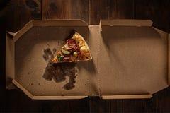 Pizzascheibe in im Lieferungskasten auf dem Holz lizenzfreie stockfotografie