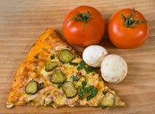 Pizzascheibe mit Tomaten lizenzfreie stockfotos