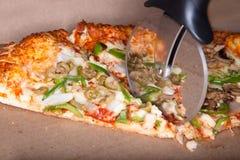 Pizzascherblock, der durch eine Pizza schneidet. lizenzfreie stockfotos