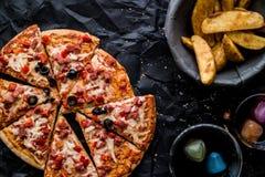 Pizzaskivor med potatiskilar och dryck på en svart yttersida & x28; Snabbmatconcept& x29; royaltyfri bild