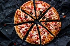 Pizzaskivor med skinka, ost och oliv på en svart yttersida Arkivfoton