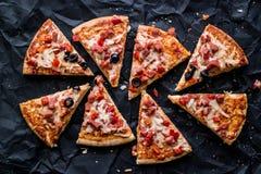 Pizzaskivor med skinka, ost och oliv på en svart yttersida Royaltyfri Fotografi