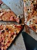 Pizzaskivor på en träplatta arkivfoto