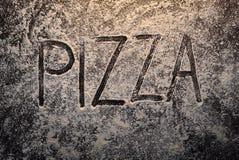Pizzatext auf Draufsicht des Mehls Stockfotografie