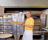 Pizzatillverkare som tar bort pizza från ugnen Fotografering för Bildbyråer