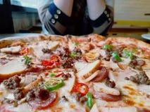 Pizzatoppningar med kvinnan på den motsatta sidan av tabellen Royaltyfri Bild
