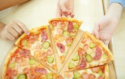In pizzeria. Children taking pieces of pizza royalty free stock photos