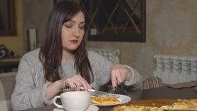 pizzeria Giovane donna che mangia pizza ad un caffè stock footage