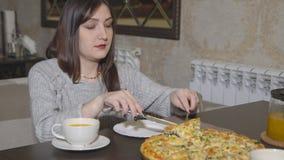 pizzeria La giovane donna prende una fetta di pizza con la coltelleria stock footage