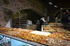 Pizzeria shop with the counter full of different true Italian pizzas. stock image