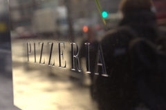 Pizzeria sign. On glass window reflecting person walking in street Royalty Free Stock Images