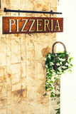 Pizzeria sign on wall with decorative flowerpot Stock Image