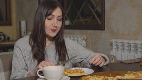 pizzeria Una donna castana che mangia pizza ad un caffè archivi video