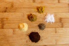 6 pizzichi delle erbe variopinte e delle spezie sul tagliere Fotografia Stock Libera da Diritti