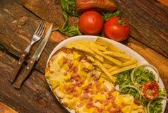 Pizzy i francuza nad widok wyśmienicie dłoniaki, pomidor, marchewka, rozwidlenie i nóż na drewnianym stole przygotowywającym jeść obraz stock