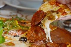 Pizzy polewy salami i kiszony oliwny rozciąganie ser na ręce Zdjęcie Stock