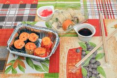 Pizzy sushiThe skład na tnącej deski suszi dla fasta food i pizzy Drewniani kije dla suszi Świeży gorący jedzenie obrazy stock