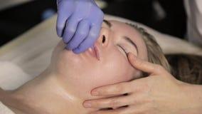 Plástico do contorno o esteticista faz a massagem do bordo para a mulher bonita no bar da beleza filme