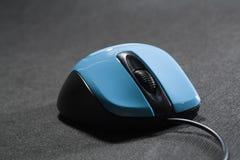 Plástico do rato do computador pequeno Cor azul Fundo preto Fio preto Um espaço vazio para uma inscrição Eletrônica fotografia de stock