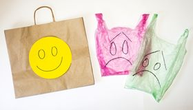 Plástico e sacos de papel com emoções felizes e tristes nas caras contra o fundo branco fotos de stock royalty free