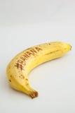 Plátano con el fondo blanco y texto en la fruta Foto de archivo libre de regalías