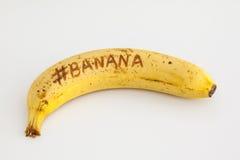 Plátano con el fondo blanco y texto en la fruta Foto de archivo