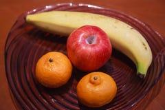 Plátano estacional asiático fresco tropical de la porción de las frutas, manzana roja, naranjas de la mandarina en la habitación  fotografía de archivo