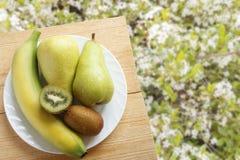 Plátano, fruta de kiwi y pera frescos en la tabla de madera en el fondo de hierbas verdes con las flores blancas Concepto sano de Imagen de archivo libre de regalías