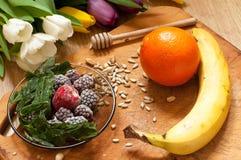 plátano, naranja, zarzamoras congeladas de las fresas e ingredientes vivos del smoothie de las semillas en el fondo Imágenes de archivo libres de regalías