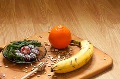 plátano, naranja, zarzamoras congeladas de las fresas e ingredientes vivos del smoothie de las semillas en el fondo Imagenes de archivo