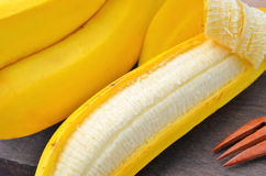 Plátano pelado en el fondo de madera Imagen de archivo