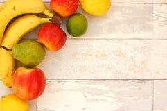 Plátano, pera, cal, manzanas y limones en la esquina en el fondo de madera Fotos de archivo libres de regalías