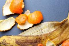 Plátano y cáscaras de naranja en el fondo gris, cierre para arriba Fotografía de archivo libre de regalías